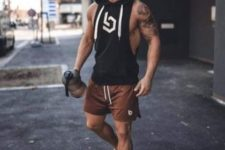 rust shorts, white trainers and a black sleeveless hoodie for a super stylish sporty look
