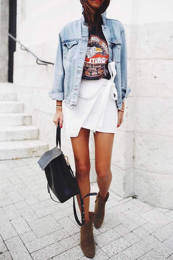 a black printed tee, a white asymmetrical mini skirt, a bleached denim jacket, taupe boots and a backpack