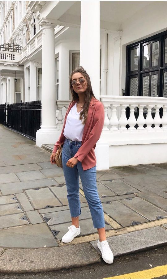 a casual outfit with a coral blazer, a white top, blue jeans, white sneakers and a woven bag to transition from summer to fall