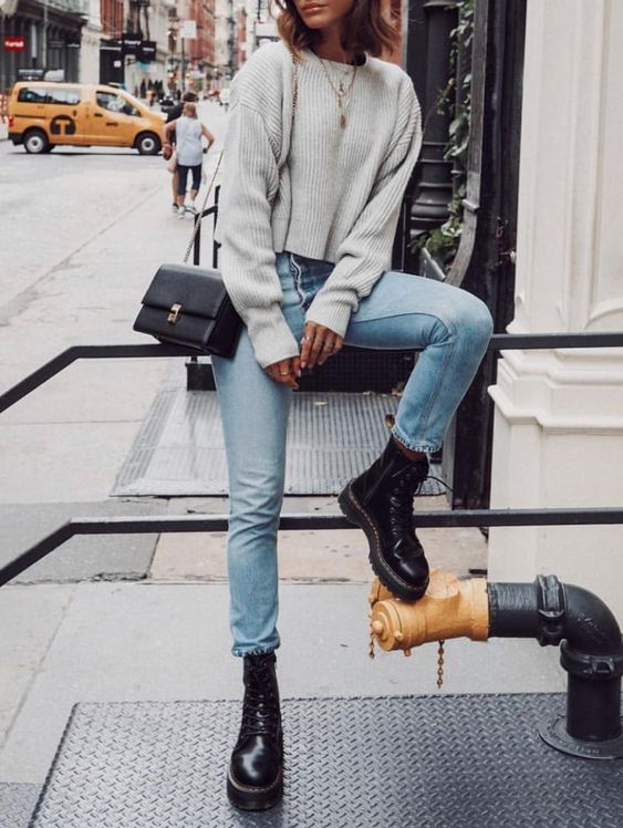a cropped oversized grey sweater, blue jeans and black platform shoes plus a black bag
