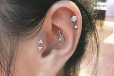03 a little spiderweb stud in the upper conch, a double helix piercing and a double tragus one