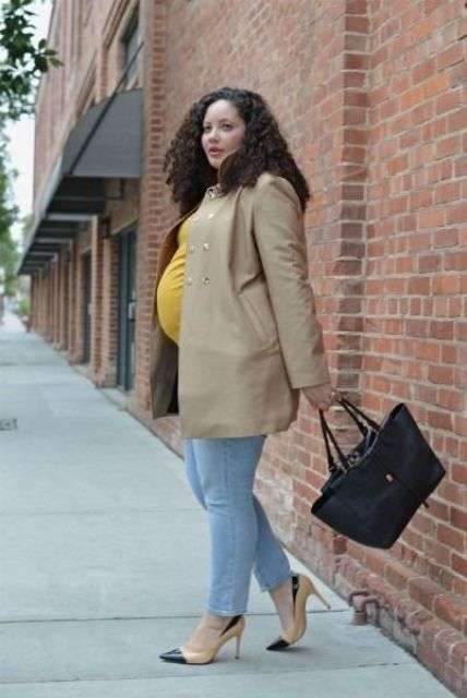 a mustard top, bleached jeans, a camel short coat, two toned shoes and a black bag