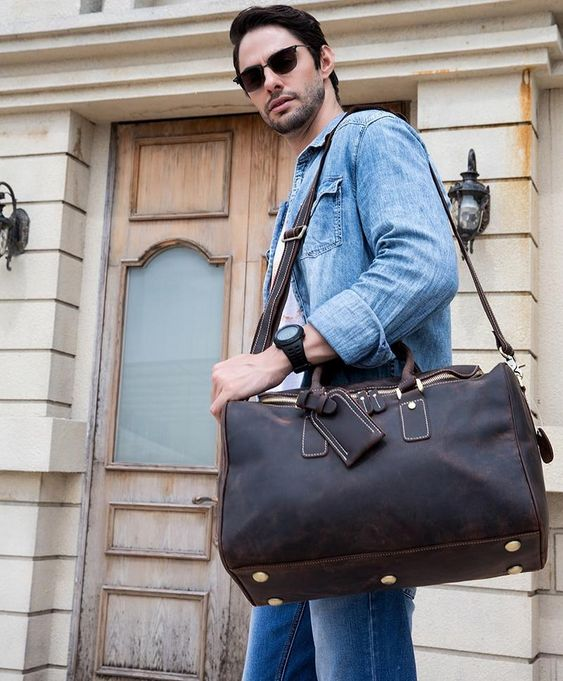 a small dark brown leather travel bag with a tag and gold hardware for a stylish manly look
