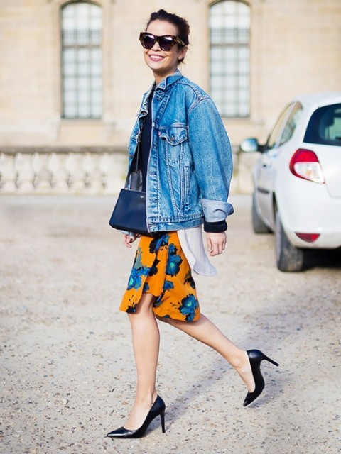 a black top, a bright floral knee skirt, an oversized denim jacket and black heels for a bold look