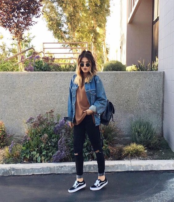 a rust-colored tee, black ripped jeans, black sneakers, a blue denim jacket and a black backpack