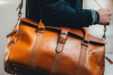 04 an amber leather bag with multiple belts and a long handle to carry it crossbody