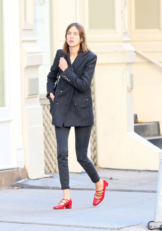black skinnies, a black oversized short coat, red Mary Jane shoes and a black bag