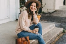 05 a simple and relaxed look with blue ripped jeans, a neutral oversized sweatshirt, sandals and a brown hat plus a rust-colored bag