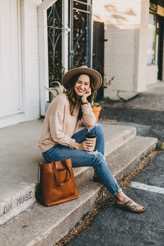 a simple and relaxed look with blue ripped jeans, a neutral oversized sweatshirt, sandals and a brown hat plus a rust-colored bag