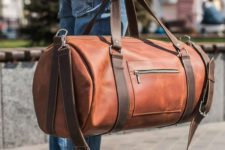 05 an amber leather tube-like travel bag with brown belts is a very modern and bold idea