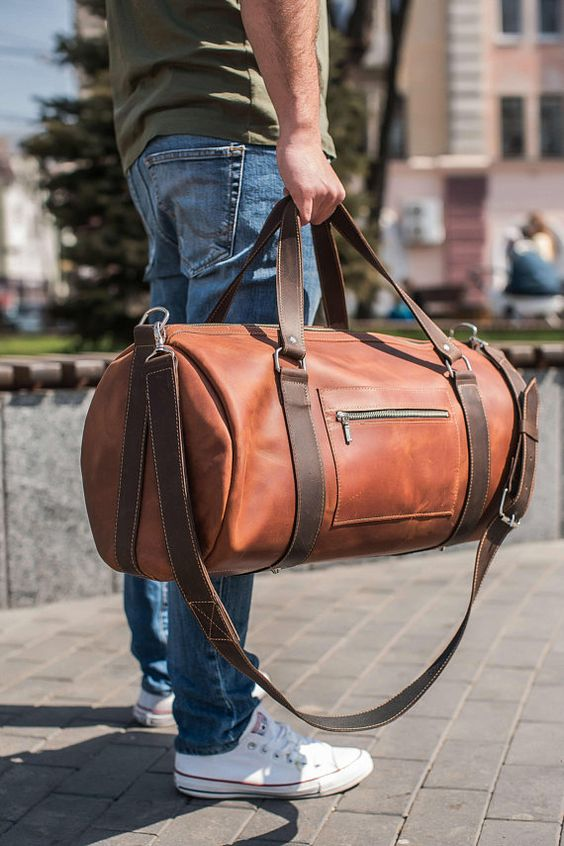 an amber leather tube-like travel bag with brown belts is a very modern and bold idea