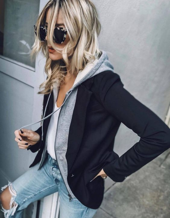 blue ripped jeans, a white top, a grey hoodie and a black blazed over it for a chic casual look