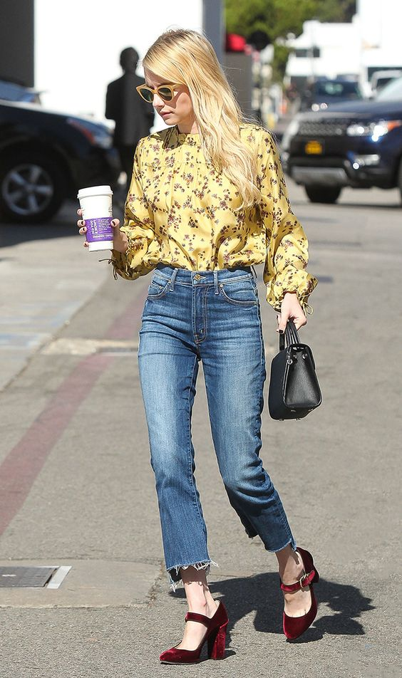 Emma Roberts wearing a vintage yellow floral blouse, blue jeans, burgundy velvet Mary Jane shoes and a black bag