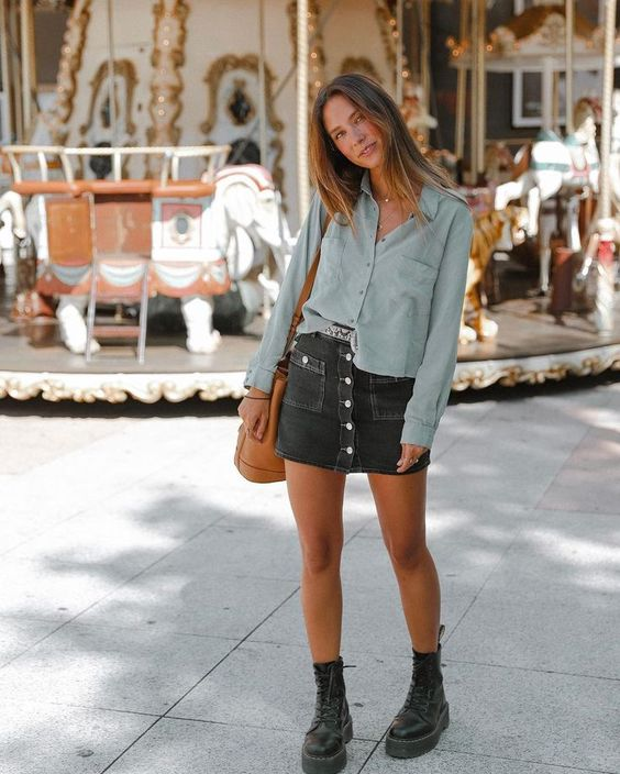 a grey shirt, a black denim mini skirt with a row of buttons, black boots and an amber bag