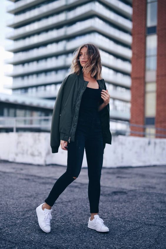 a simple look with black ripped jeans, a black top, white sneakers and a grene bomber jacket for chilly weather