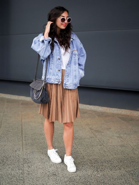 a white tee, a camel pleated knee skirt, white sneakers, a blue denim jacket and a graphite grey bag