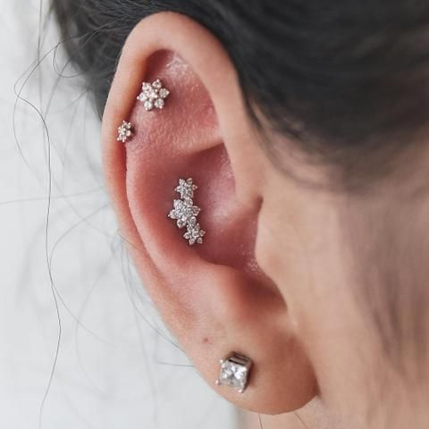 shiny floral studs in the daith, conch and a simple and stylish stud in the lap