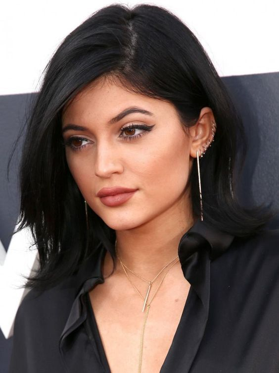 Kylie Jenner rocking lots of piercing hoops in her ear looks super rock and cool