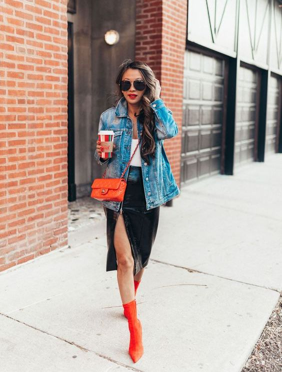 a white top, a black velvet midi skirt with a thigh high slit, a blue denim jacket, orange sock boots and a matching bag