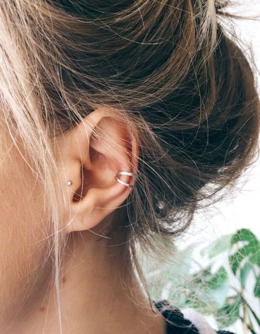 two silver hoops in the helix and a sud earring in the tragus for a trendy and modern look