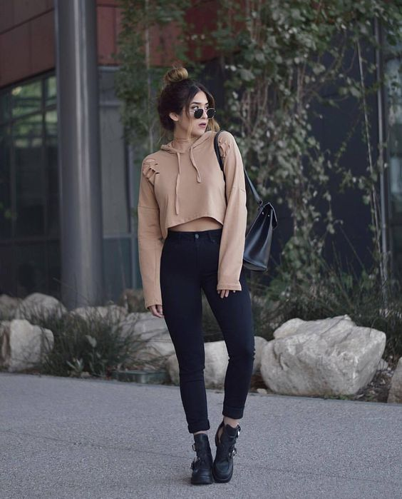 a cropped nude hoodie, black high waisted skinnies, black boots and sunglasses for a bit of edge