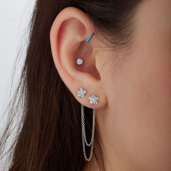 a double lap piercing, a helix one and an inner conch piercing with bright studs are a chic idea