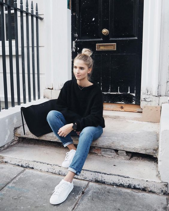 blue jeans, white sneakers and a black sweatshirt plus a large black bag for a casual weekend look