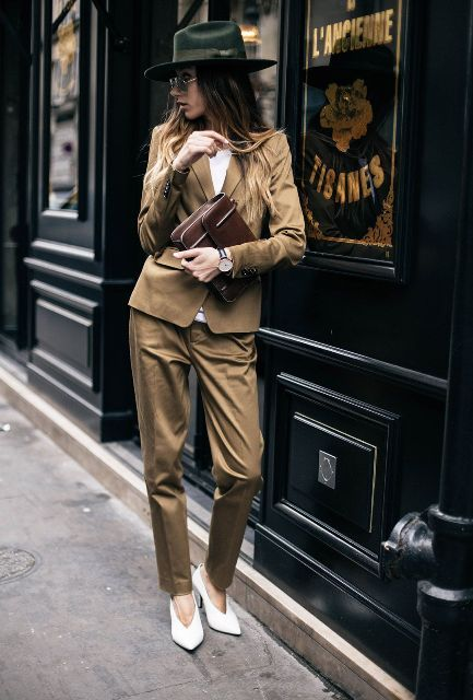 a camel pantsuit, a white top, white V cut shoes and a black hat for a chic and bold look