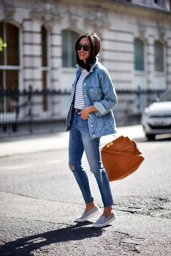 a striped tee, blue ripped skinnies, an oversized denim jacket, grey slipons and a camel bag