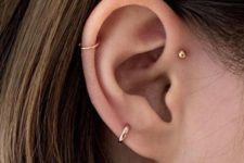 10 a double helix piercing with two hoops and a gold stud for a bold and modern feel