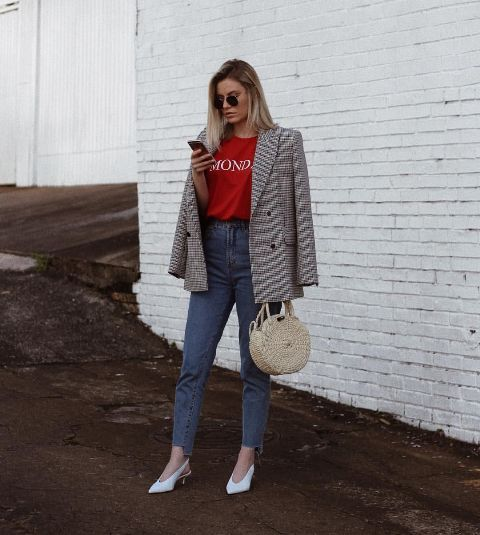 a red printed tee, blue jeans, white V cut slingbacks, a tweed blazer and a wicker bag