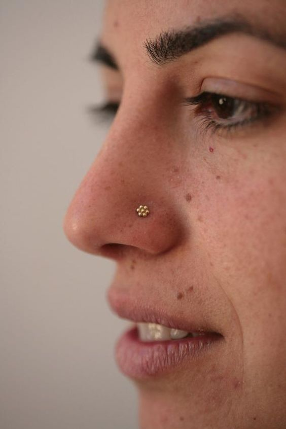 a tiny gold floral piercing for a girly touch and a bling on your face