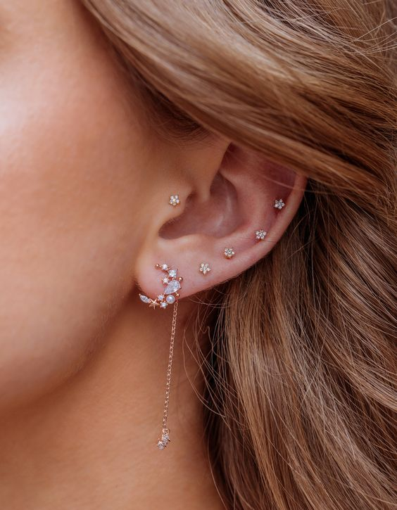 beautiful ear accessorizing with little floral studs including helix and tragus piercing