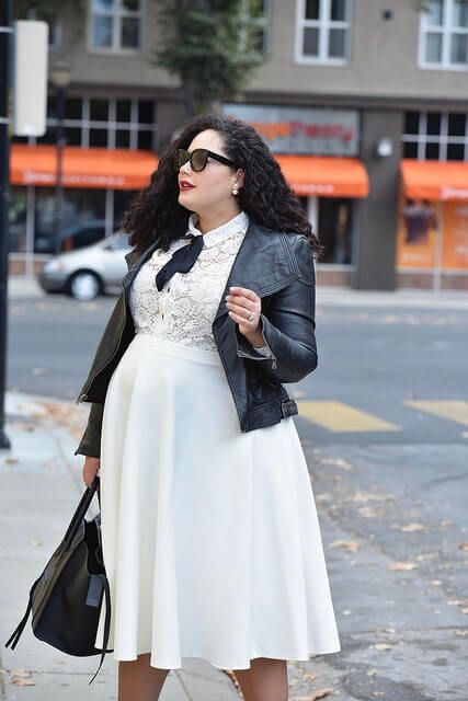 a beautiful white dress with a lace bodice, a plain skirt, a black bow, a black leather jacket and a black tote