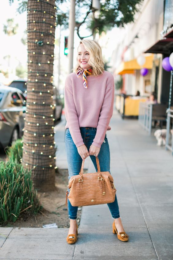 a pink sweater, blue jeans, a camel crocodile leather bag and camel heeled loafers