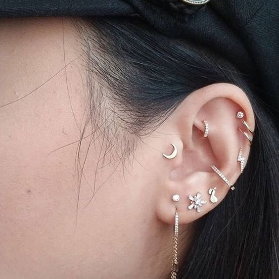 bold ear accessorizing with all kind sof piercings including tragus, with hoops and studs in the same style