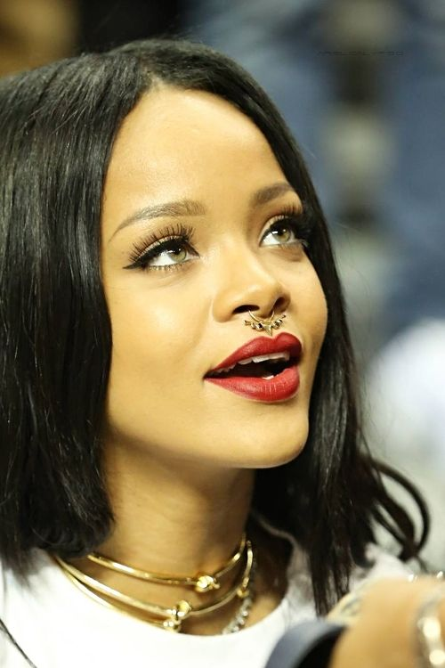 Rihanna wearing a gorgeous embellished nose hoop piercing and layered necklaces for a wild touch