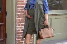 12 a blue chambray shirt, long olive waistcoat, a matching skirt, lace up shoes and a brown bag