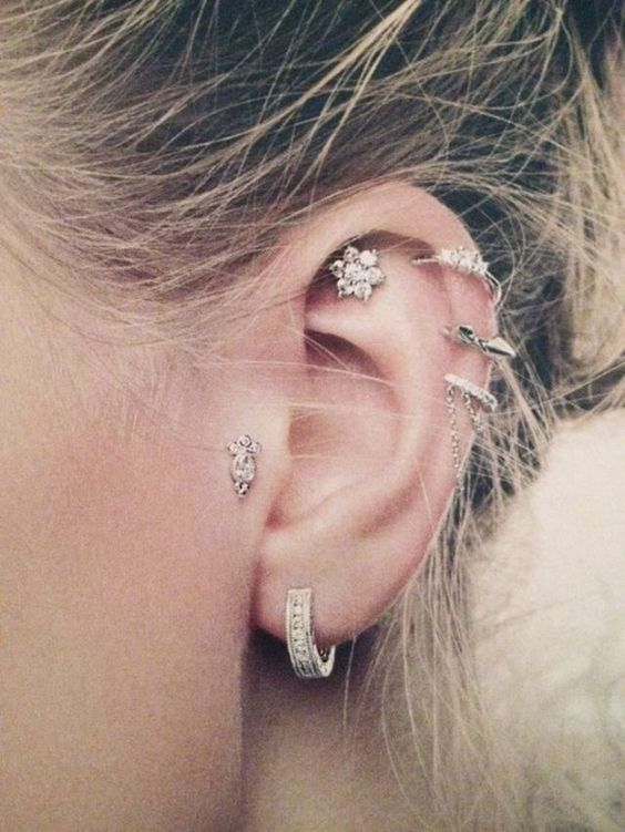 bold ear accessorizing with three helix hoops, a daith floral stud and a stud tragus piercing