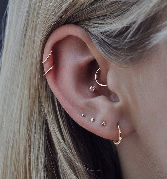elegant multiple ear piercings with studs and hoops including the conch, helix and lap