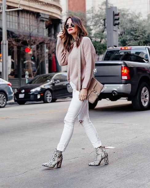 white ripped skinnies, a blush oversized sweater, snake print boots and a neutral bag