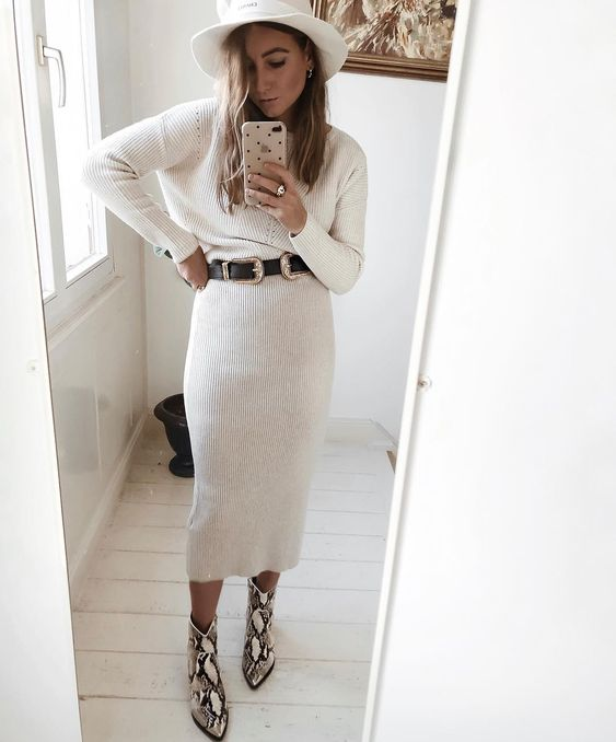 a creamy sweater dress accented with a black belt, a white hat and snake print cowboy boots