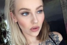 13 a statement tattoo and a nose hoop piercing make the girl's look super bold and outstanding