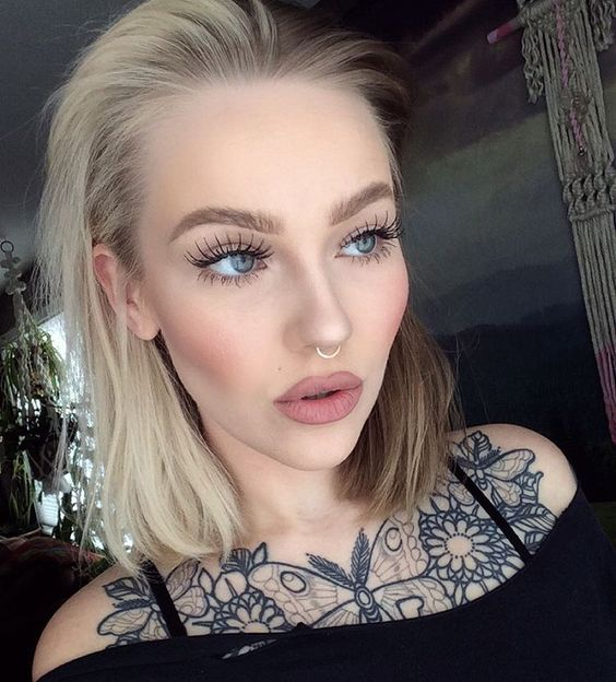 a statement tattoo and a nose hoop piercing make the girl's look super bold and outstanding