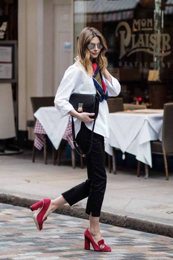 a white oversized shirt, black velvet pants, a black bag and red heeled loafers for an accent