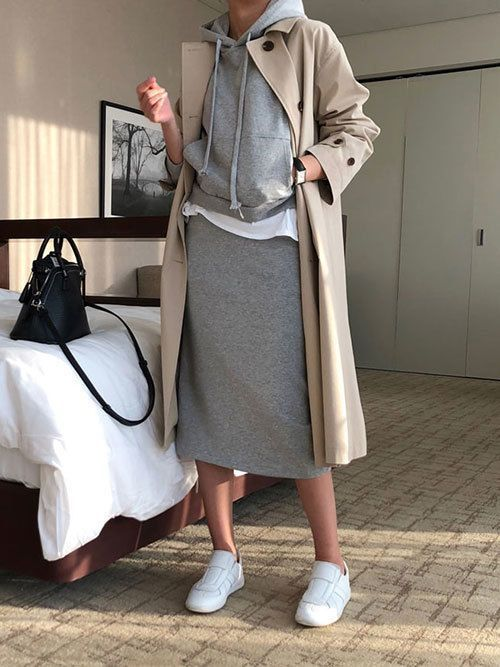 a white shirt, a grey midi skirt, a grey hoodie, a neutral trench and white sneakers