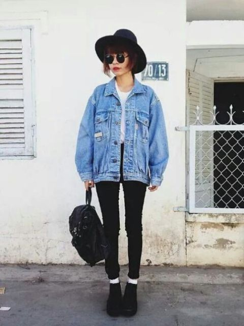 black skinnies, a white tee, black boots, a blue denim jacket, a black backpack and a hat