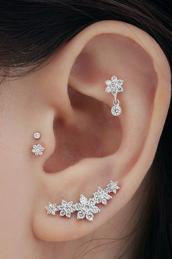 gorgeous ear accessorizing with daith, lap and double tragus piercing with shiny rhinestone floral studs