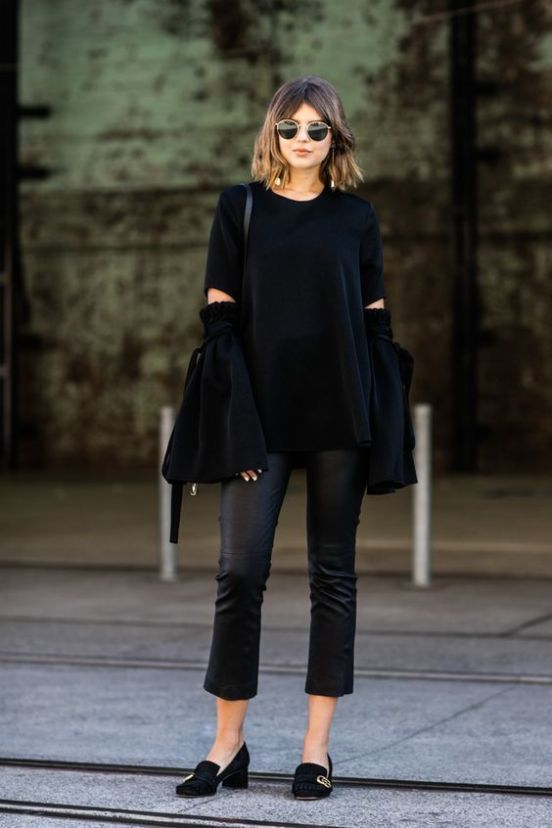 a black oversized ripped sweater, black leather pants, a black bag and heeled loafers