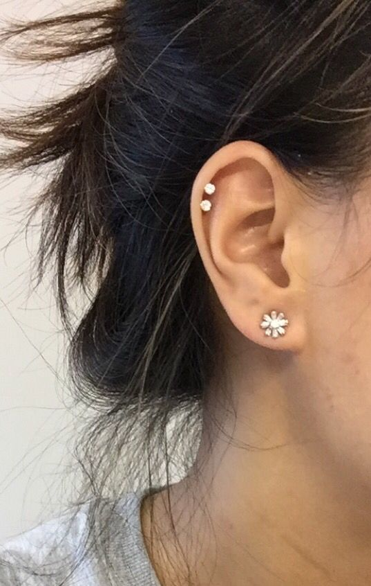 a floral earring and two piercings in the helix are a cool and fresh idea to try
